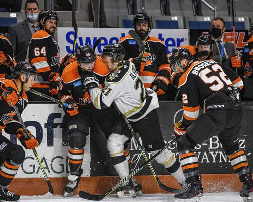 Photos by Mike Moore | The Journal Gazette Wheeling forward Matt Alfaro is crushed by Justin Vaive in front of the Komets bench on Friday at Memorial Coliseum.