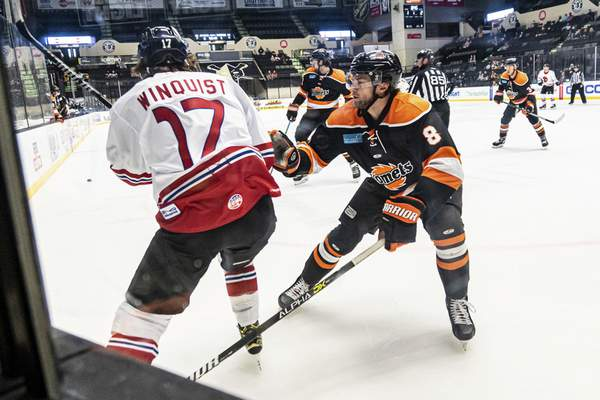 Zack Rawson | Special to The Journal Gazette  The Komets' Blake Siebenaler, right, prepares to check the Wheeling Nailers' Joshua Winquist, who had just passed the puck up the boards in Wheeling, West Virginia.
