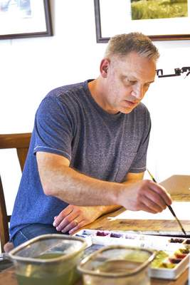 Katie Fyfe | The Journal Gazette  Watercolor artist Tom De Sommer pictured in his studio attached to his home on Friday, March 23rd, 2021.