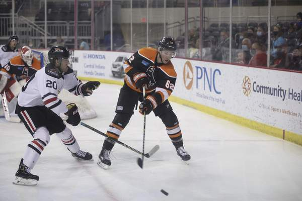 Whiteshark Photography  The Komets' Olivier Galipeau, right, sends the puck up the boards Sunday as he's defended by the Indy Fuel's Alex Rauter in Indianapolis.
