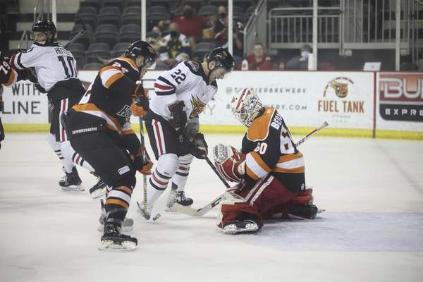 Whiteshark Photography Komets goaltender Robbie Beydoun readies to stop the puck as the Indy Fuel's Jared Thomas and Fort Wayne's Matt Murphy look for control.