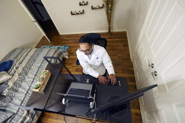 Associated Press Dr. Vibin Roy, with virtual care provider Doctor on Demand, listens to a patient during an online visit from his home in Keller, Texas.