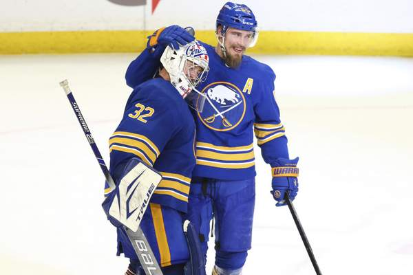Buffalo Sabres goalie Michael Houser (32) celebrates a victory over the New York Islanders with Defenseman Rasmus Ristolainen (55) following the third period of an NHL hockey game against the New York Islanders, Monday, May 3, 2021, in Buffalo, N.Y. (AP Photo/Jeffrey T. Barnes)