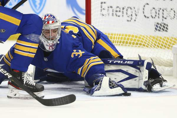 Buffalo Sabres goalie Michael Houser (32) covers the puck during the second period of an NHL hockey game against the New York Islanders, Monday, May 3, 2021, in Buffalo, N.Y. (AP Photo/Jeffrey T. Barnes)