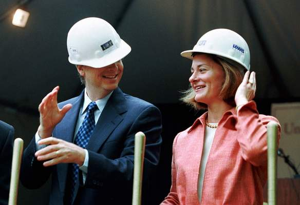 FILE - In this May 4, 2001, file photo, Microsoft Chairman Bill Gates contends with an ill-fitting hard hat while his wife, Melinda Gates, looks on in Seattle at the groundbreaking of the University of Washington's new law school facility, William H. Gates Hall. The couple announced Monday, May 3, 2021, that they are divorcing. (AP Photo/Andy Rogers, File)