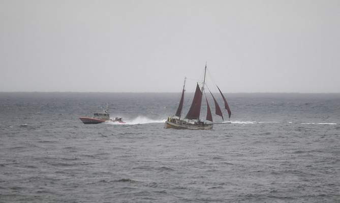 A U.S. Coast Guard boat goes past a sailboat during a search effort near where a boat capsized just off the San Diego coast Sunday, May 2, 2021, in San Diego. (AP Photo/Denis Poroy)