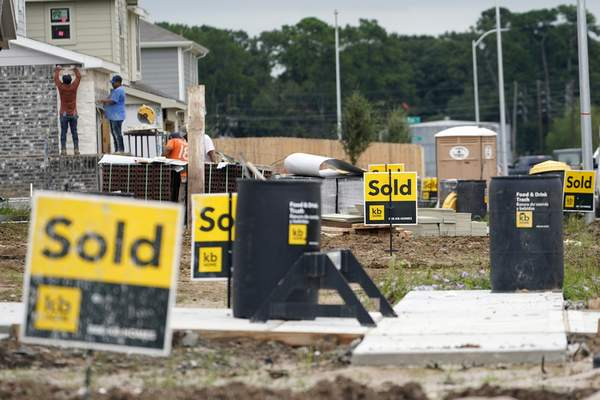 FILE - In this Sept. 24, 2020, file photo, construction workers build already sold new KB Homes in Houston. (AP Photo/David J. Phillip, File)