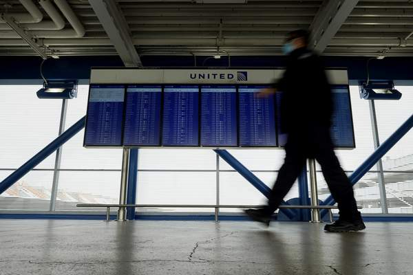 FILE - In this Oct. 14, 2020 file photo, a TSA staff wears mask as he walks past flight information screens show flight status information at O'Hare International Airport in Chicago. (AP Photo/Nam Y. Huh)