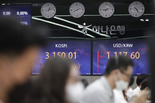 Currency traders work near screens showing the Korea Composite Stock Price Index (KOSPI), left, and the foreign exchange rate between U.S. dollar and South Korean won at a bank's foreign exchange dealing room in Seoul, South Korea, Monday, May 3, 2021. (AP Photo/Lee Jin-man)