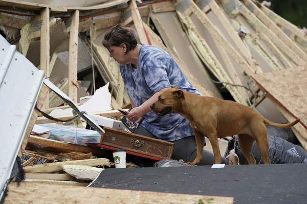 Associated Press Vickie Savell looks through her belongings amid the remains of her new mobile home early Monday in Yazoo County, Miss. Multiple destructive tornadoes were reported across the South on Sunday and Monday.