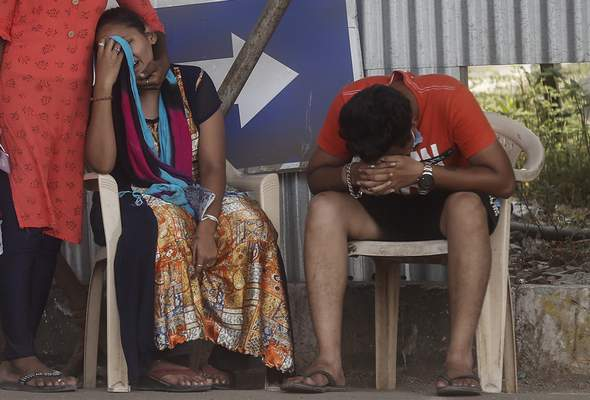 Associated Press Relatives of a person who died of COVID-19 mourn Monday outside a field hospital in Mumbai, India.