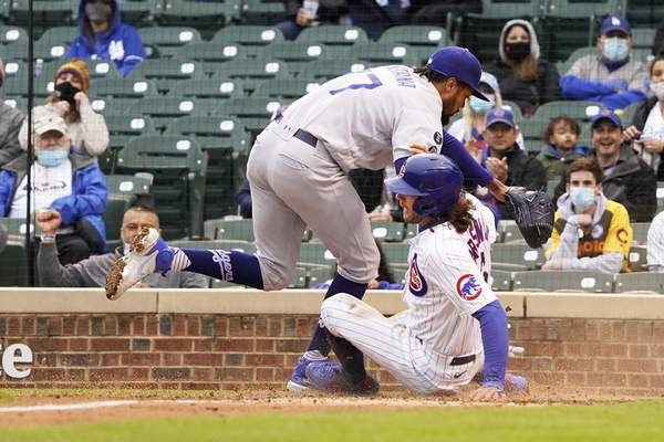 Chicago Cubs' Jake Marisnick, right, slides safely into home plate as Los Angeles Dodgers relief pitcher Dennis Santana (77) tries to make a tag during the third inning of the first baseball game of a doubleheader Tuesday, May, 4, 2021, in Chicago. (AP Photo/David Banks)