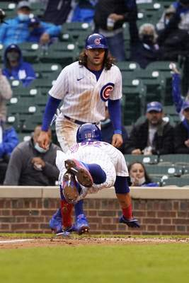 Chicago Cubs' Ildemaro Vargas, bottom, slides safely into home plate as teammate Jake Marisnick, top, stands nearby during the third inning of the first baseball game of a doubleheader against the Los Angeles Dodgers Tuesday, May, 4, 2021, in Chicago. (AP Photo/David Banks)