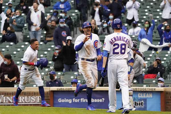 Chicago Cubs' Ildemaro Vargas, left and Jake Marisnick, center, celebrate after scoring on a wild pitch against the Los Angeles Dodgers as Kyle Hendricks (28) stands nearby during the third inning of the first baseball game of a doubleheader Tuesday, May, 4, 2021, in Chicago. (AP Photo/David Banks)