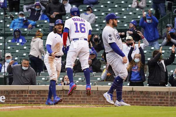 Chicago Cubs' Ildemaro Vargas, center, and Jake Marisnick, left, celebrate as they both scored on a wild pitch as Los Angeles Dodgers first baseman Max Muncy, right, stands nearby during the third inning of the first baseball game of a doubleheader Tuesday, May, 4, 2021, in Chicago. (AP Photo/David Banks)