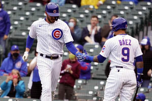 Chicago Cubs' Kris Bryant, left, is greeted by Javier Baez (9) after scoring against the Los Angeles Dodgers during the first inning of the first baseball game of a doubleheader Tuesday, May, 4, 2021, in Chicago. (AP Photo/David Banks)