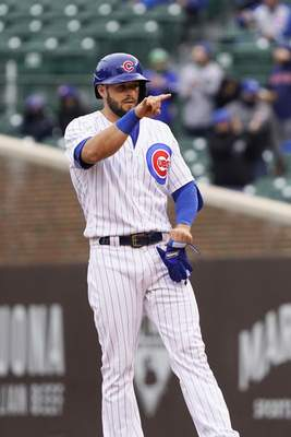 Chicago Cubs' David Bote gestures after hitting a three run double against the Los Angeles Dodgers during the first inning of the first baseball game of a doubleheader Tuesday, May, 4, 2021, in Chicago. (AP Photo/David Banks)