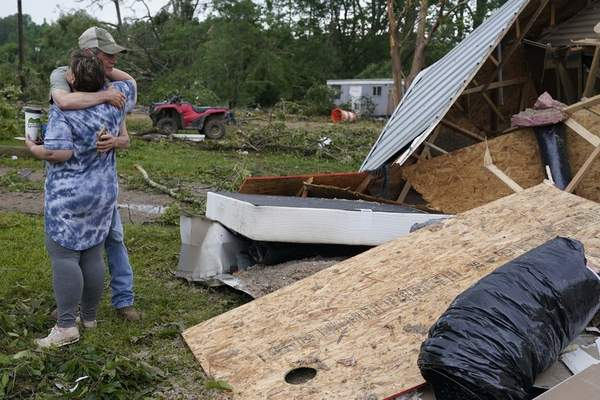 A neighbor hugs Vickie Savell next to the remains of her new mobile home early Monday, May 3, 2021, in Yazoo County, Miss. (AP Photo/Rogelio V. Solis)