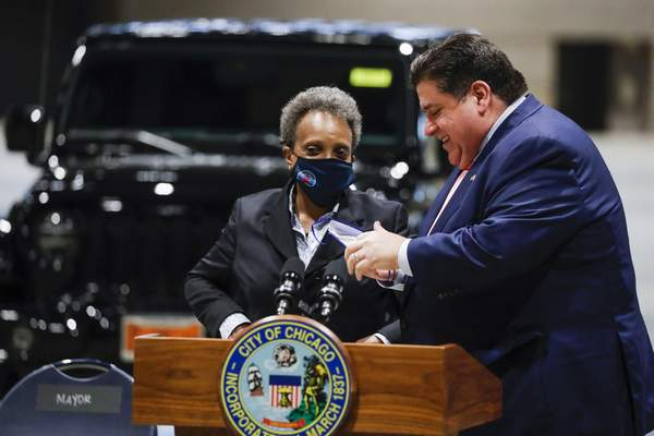 Governor J.B. Pritzker and Mayor Lori Lightfoot talk following a news conference regarding updates on Chicago's reopening efforts at McCormick Place in Chicago on Tuesday, May 4, 2021. (Jose M. Osorio /Chicago Tribune via AP)