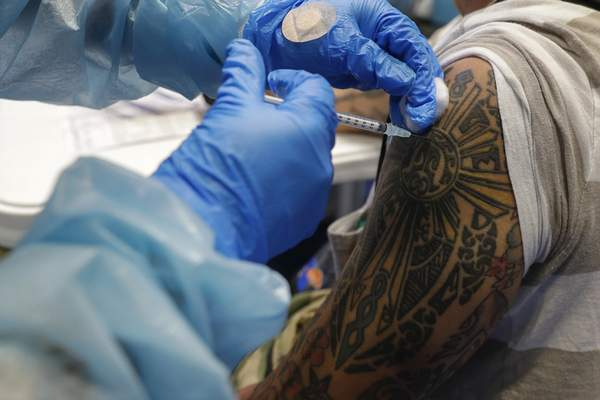 A health worker inoculates a man with tattoos with China's Sinovac COVID-19 vaccine inside the Makati Coliseum, Metro Manila, Philippines on Tuesday, May 4, 2021. (AP Photo/Aaron Favila)