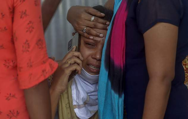 FILE - In this May. 3, 2021, file photo, relatives of a person who died of COVID-19 mourn outside a field hospital in Mumbai, India. COVID-19 infections and deaths are mounting with alarming speed in India with no end in sight to the crisis. (AP Photo/Rafiq Maqbool, File)