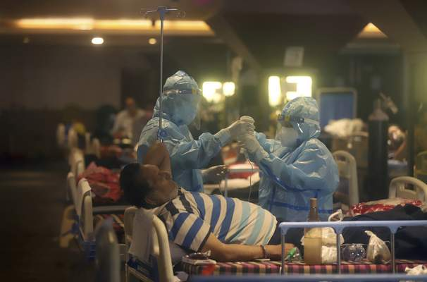 FILE - In this April 30, 2021, file photo, health workers attend to COVID-19 patients at a makeshift hospital in New Delhi, India. (AP Photo/File)