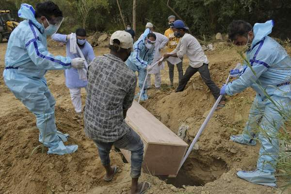 Relatives bury the body of a COVID-19 victim at a graveyard in New Delhi, India, Tuesday, May 4, 2021. (AP Photo/Ishant Chauhan)