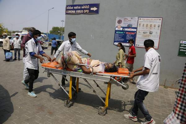 FILE - In this April 27, 2021, file photo, health workers bring a patient to be admitted at a government COVID-19 hospital in Ahmedabad, India. (AP Photo/Ajit Solanki, File)