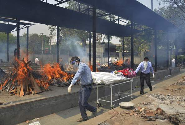 FILE - In this May 1, 2021, file photo, relatives carry the body of a person who died of COVID-19 as multiple pyres of other COVID-19 victims burn at a crematorium in New Delhi, India. (AP Photo/Amit Sharma, File)