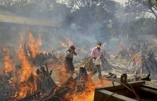 FILE - In this April 29, 2021, file photo, relatives react to heat emitting from the multiple funeral pyres of COVID-19 victims at a crematorium in the outskirts of New Delhi, India. (AP Photo/Amit Sharma, File)
