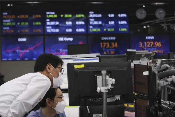 Currency traders watch monitors at the foreign exchange dealing room of the KEB Hana Bank headquarters in Seoul, South Korea, Tuesday, May 4, 2021. (AP Photo/Ahn Young-joon)
