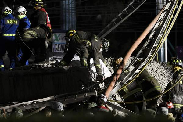 Rescue personnel retrieve bodies from the scene of an accident where subway cars fell after a section of Line 12 of the subway collapsed in Mexico City, Tuesday, May 4, 2021. (AP Photo/Marco Ugarte)