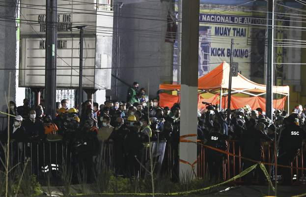 Media and onlookers are kept behind a police tape at the scene where subway cars fell after a section of Line 12 of the subway collapsed in Mexico City, Tuesday, May 4, 2021. (AP Photo/Marco Ugarte)
