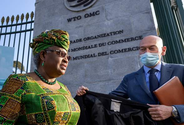 FILE - In this Monday, March 1, 2021 file photo, New Director-General of the World Trade Organisation Ngozi Okonjo-Iweala, left, walks at the entrance of the WTO, following a photo-op upon her arrival at the WTO headquarters to take office in Geneva, Switzerland. (Fabrice Coffrini/Pool/Keystone via AP, FIle)