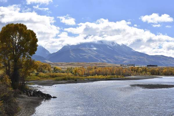 FILE - In this Oct. 8, 2018, file photo, Emigrant Peak is seen rising above the Paradise Valley and the Yellowstone River near Emigrant, Mont. (AP Photo/Matthew Brown, File)