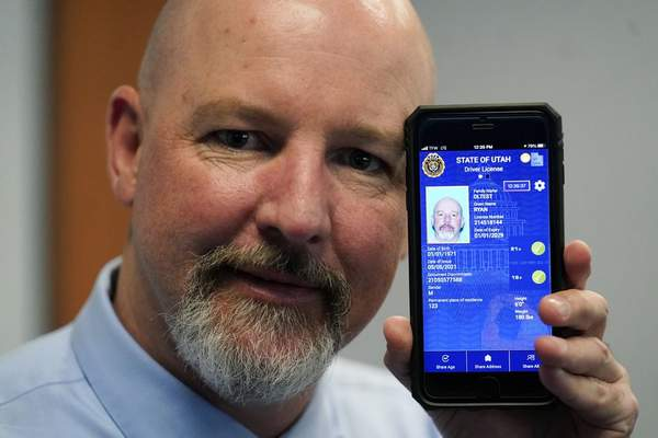 Ryan Williams, with the Utah Drivers License Division, displayes his cell phone with the pilot version of the state's mobile ID on Wednesday, May 5, 2021, in West Valley City, Utah. (AP Photo/Rick Bowmer)