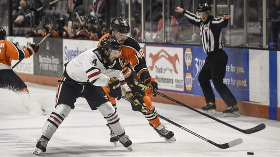 Mike Moore | The Journal Gazette Fuel defenseman Tim Shoup, left and Komets forward Justin Vaive race for the puck in the first period at Memorial Coliseum on Saturday.