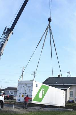 Michelle Davies | The Journal Gazette A shipping container is lowered into position behind CASS Housing's office Friday morning. The container will serve as a hydroponic farm.
