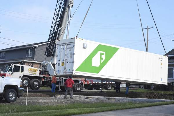 Michelle Davies | The Journal Gazette  A shipping container, one of two, that will be part of a hydroponic farm, is lowered into position behind CASS Housing's office Friday morning.