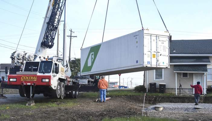 Michelle Davies | The Journal Gazette  A container, one of two, that will be part of a hydroponic farm, is lowered into position behind CASS Housing's office Friday morning.
