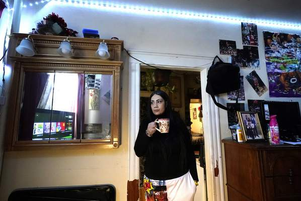 FILE- In this March 10, 2021, file photo, Isabel Miranda drinks coffee in her rental apartment where she lives with her partner and two sons, in Haverhill, Mass. (AP Photo/Elise Amendola, File)