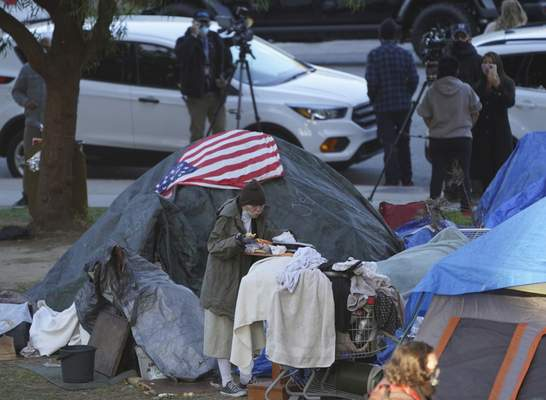 FILE - In this March 24, 2021, file photo a woman eats at her tent at the Echo Park homeless encampment at Echo Park Lake in Los Angeles. (AP Photo/Damian Dovarganes, File)