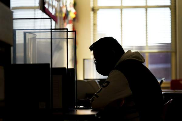 Senior Jose Solano-Hernandez takes a test on the first day of in-person learning at Wyandotte High School in Kansas City, Kan., Wednesday, March 30, 2021. (AP Photo/Charlie Riedel)