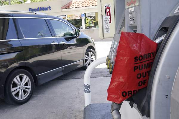 A customer drives from a Chevron station after it ran out of gasoline, Wednesday, May 12, 2021, in Miami. (AP Photo/Marta Lavandier)