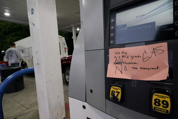 A hand written sign is posted on a gas pump, showing that the service station is out of all grades of fuel Wednesday, May 12, 2021, in Charlotte, N.C. (AP Photo/Chris Carlson)