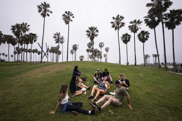 FILE - In this May 5, 2021, file photo, a group of friends, who said they are fully vaccinated for COVID-19, mingle on the beach in the Venice section of Los Angeles. (AP Photo/Jae C. Hong, File)