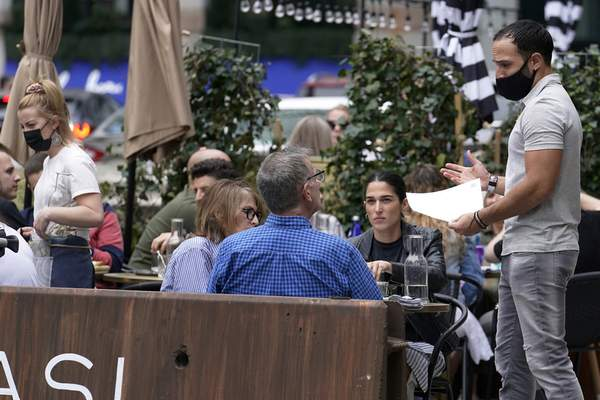 FILE - In this May 2, 2021, patrons at a sidewalk cafe are seated without masks in Boston. (AP Photo/Steven Senne, File)