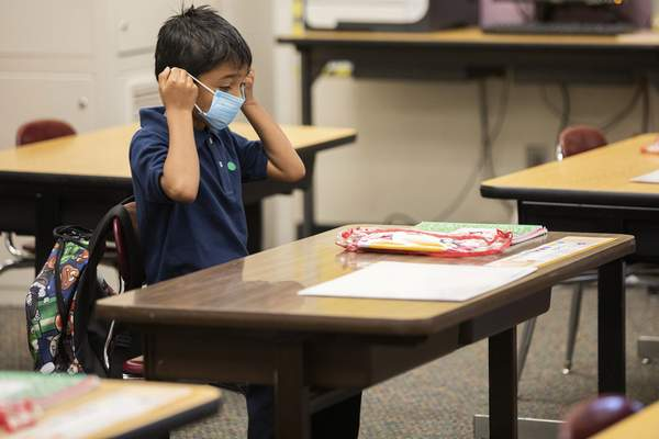 FILE - In this March 30, 2021, file photo, second grader Ernesto Beltran Pastrana puts on his face mask while attending class during the first day of partial in-person instruction at Garfield Elementary School in Oakland, Calif. (Jessica Christian/San Francisco Chronicle via AP, File)
