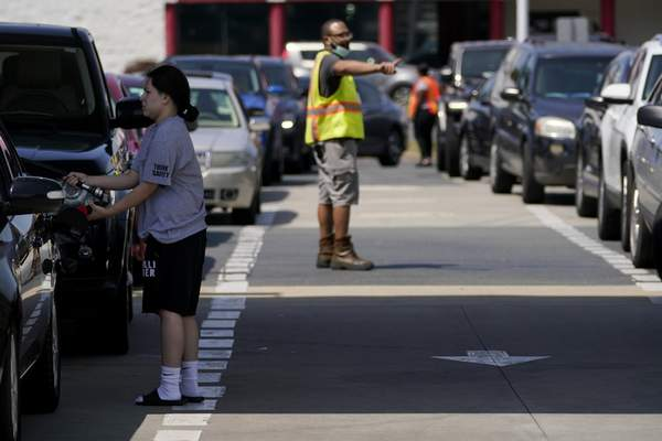 A customer pumps gas at Costco, as a worker directs traffic, on Tuesday, May 11, 2021, in Charlotte, N.C. (AP Photo/Chris Carlson)