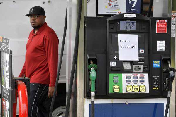 A man leaves a Murrphy Oil gas station as pumps are seen out of gas, Tuesday, May 11, 2021, in Kennesaw, Ga. (AP Photo/Mike Stewart)